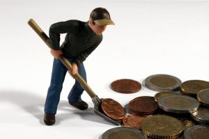 man shoveling coins