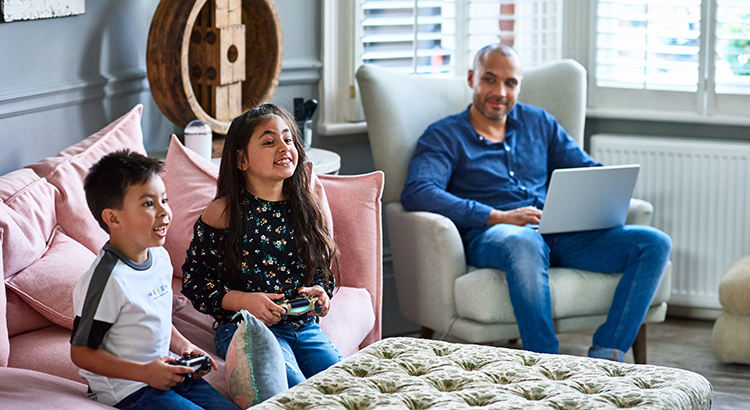 Father using laptop watching son and daughter play video game